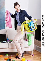 Businesswoman collecting laundry at home - Young working ...