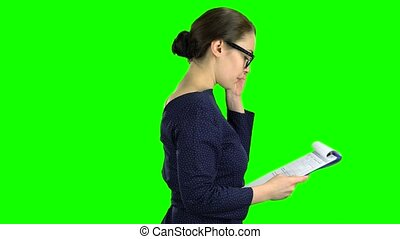 Businesswoman comes with a paper tablet on the street. Green...