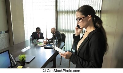 Businesswoman communicates by phone with customers during the meeting in slow motion
