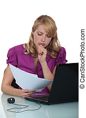 Businesswoman concentrating whilst reading document