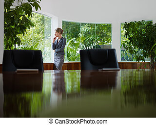 businesswoman contemplating out of window in meeting room