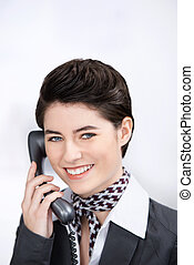 Businesswoman Conversing On Landline Phone In Office