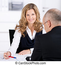 Businesswoman Conversing With Businessman At Desk