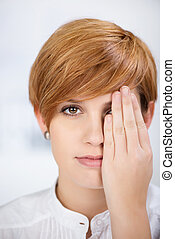 Businesswoman Covering Her One Eye With Hand - closeup...