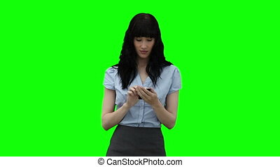 Businesswoman dialing on her mobile phone against a green...