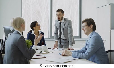 Businesswoman discussing reports with male and female...