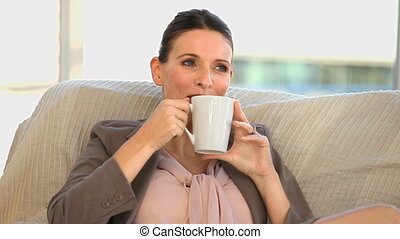 Businesswoman drinking a cup of tea on a couch