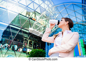 Businesswoman drinking coffee from thermo cup against office building