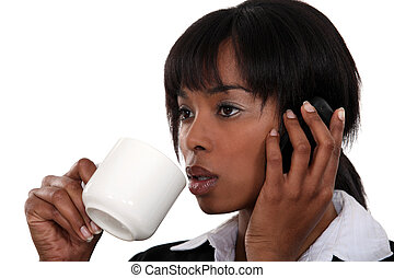 Businesswoman drinking coffee whilst telephoning