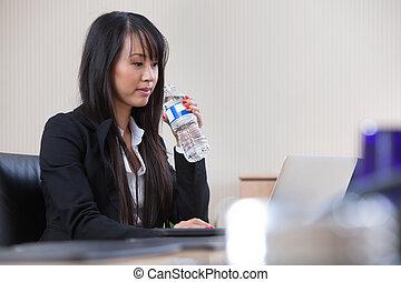 Businesswoman drinking water at work