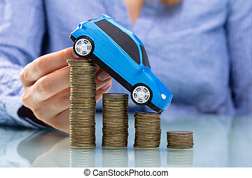 Businesswoman Driving Car On Declining Stacked Coins
