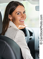 Businesswoman driving car. Rear view of confident young...