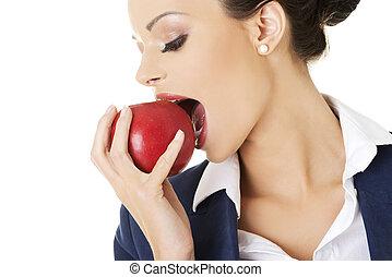 Businesswoman eating an apple