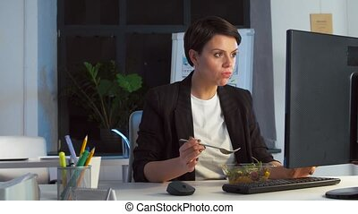 businesswoman eating and working at night office - business,...