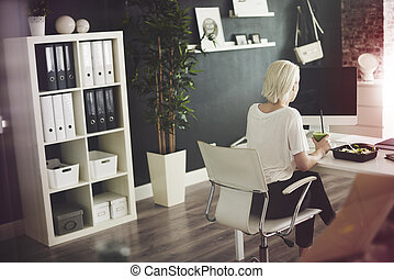 Businesswoman eating at desk in her home office