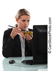businesswoman eating Chinese food in front of her screen