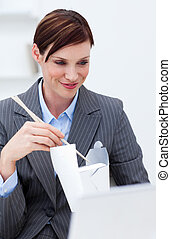 Businesswoman eating chinese food with chopstick at work