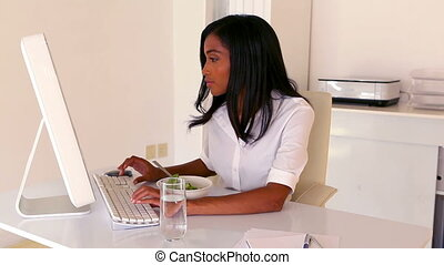 Businesswoman eating lunch at her desk in her office