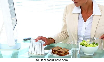 Businesswoman eating lunch at her desk - Businesswoman...