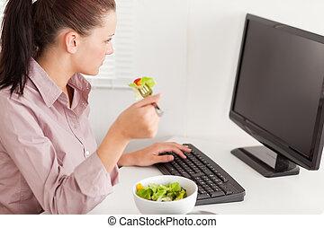Businesswoman eating salad