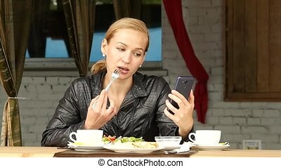 businesswoman eating salad in an outdoor cafe. girl eating...