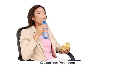 Businesswoman eating sandwich for lunch on white background