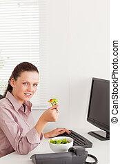 Businesswoman eats salad in her office