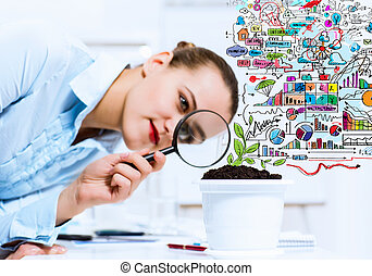 Businesswoman examining sprout - Young businesswoman looking...