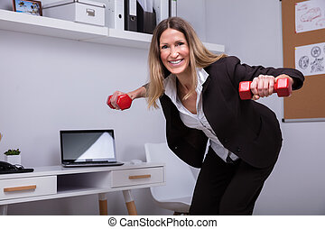 Businesswoman Exercising With Dumbbell In Office