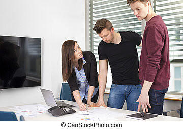 Businesswoman Explaining Plan To Coworkers At Desk