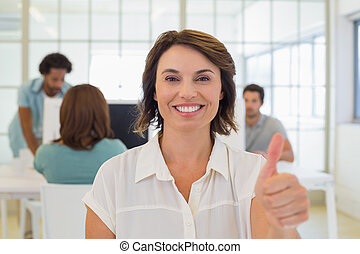 Businesswoman gesturing thumbs up with colleagues in meeting