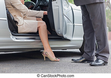 Businesswoman getting off classy cabriolet while businessman...