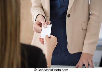 Businesswoman giving her businesscard to her partner. ...