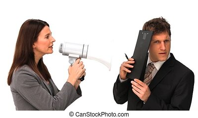 Businesswoman giving orders through a megaphone next to a...