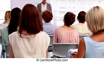 Businesswoman giving presentation to other businesswomen in...