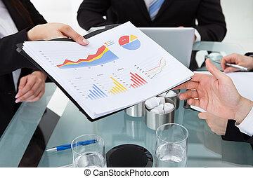 Businesswoman Giving Progress Chart To Colleague