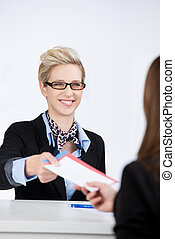 Businesswoman Giving Traveling Documents To Receptionist -...