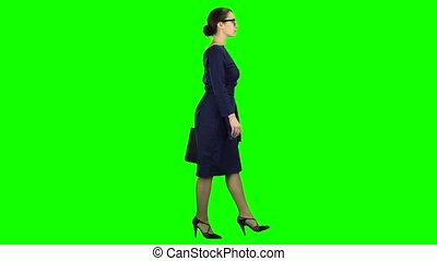 Businesswoman goes to a business meeting with a case in hand. Green screen. Side view