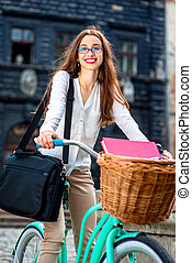 Businesswoman going to work by bicycle in old city center background