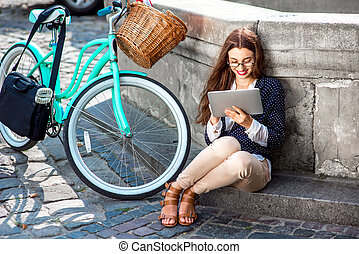 Businesswoman going to work by bicycle speaking phone in old...