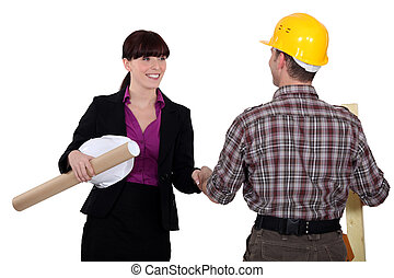 Businesswoman greeting a construction worker