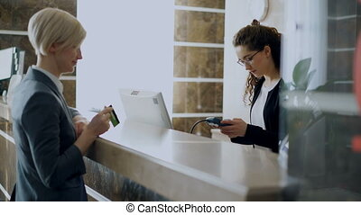 Businesswoman guest in hotel reception paying bill...