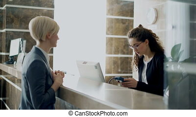 Businesswoman guest in hotel reception paying bill with...