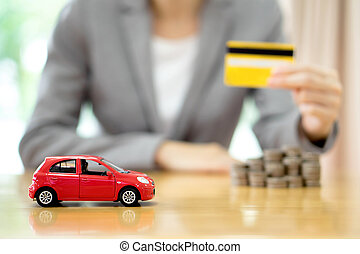 Businesswoman hand hold credit card, a toy car and a stack of coins