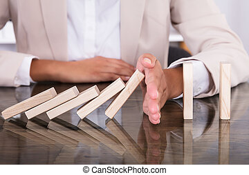 Hand Stopping Wooden Blocks From Falling