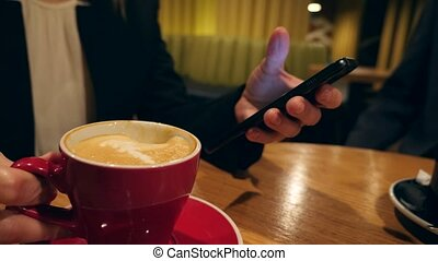 Businesswoman hands texting, sending sms on smartphone and drinking coffee in cafe. 4k, slow motion