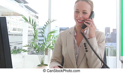 Businesswoman happy as she talks on the phone in an office