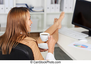 Businesswoman Having Coffee At Office Desk