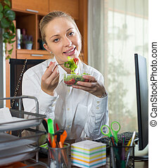Businesswoman having lunch in office