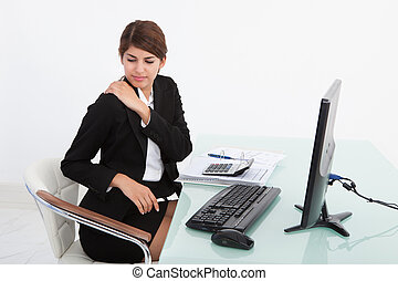 Businesswoman Having Shoulder Pain At Computer Desk